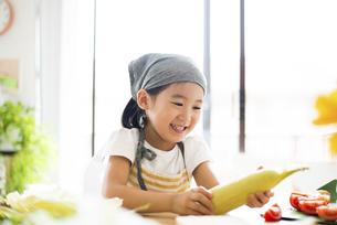 とうもろこしを持って笑っている女の子の写真素材 [FYI04823866]