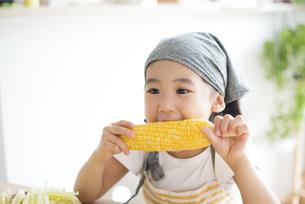 とうもろこしを食べている女の子の写真素材 [FYI04823869]