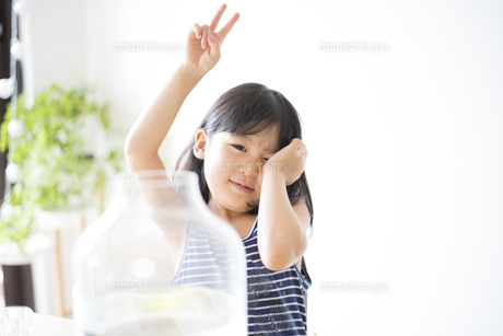 花瓶の前でピースをしている女の子の写真素材 [FYI04823871]
