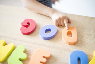 アルファベットのおもちゃで遊んでいる女の子の写真素材 [FYI04823885]