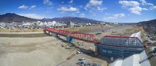 復旧工事中の別所線千曲川橋梁と上田市街と烏帽子岳の写真素材 [FYI04824087]