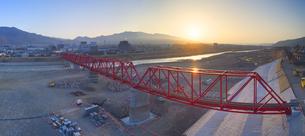 復旧工事完了後の別所線千曲川橋梁と上田市街と朝日の写真素材 [FYI04824098]