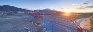 復旧工事中の別所線千曲川橋梁と上田市街と朝日の写真素材 [FYI04824111]