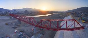 復旧工事完了後の別所線千曲川橋梁と上田市街と朝日の写真素材 [FYI04824112]