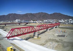 復旧工事完了後の別所線千曲川橋梁と上田市街と太郎山の写真素材 [FYI04824113]