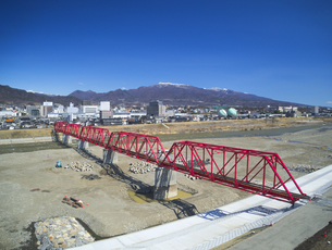 復旧工事完了後の別所線千曲川橋梁と上田市街と烏帽子岳の写真素材 [FYI04824115]