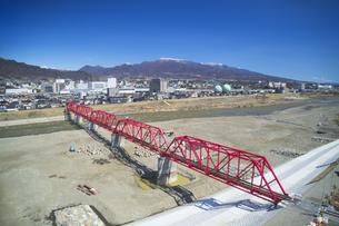 復旧工事完了後の別所線千曲川橋梁と上田市街と烏帽子岳の写真素材 [FYI04824116]