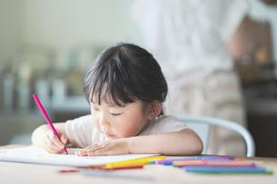 ダイニングテーブルでお絵かきをする子どもの写真素材 [FYI04824339]