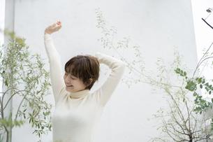ベランダで深呼吸する若い女性の写真素材 [FYI04825559]