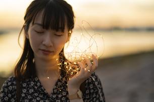 イルミネーションライトを耳に近づける若い女性の写真素材 [FYI04825569]