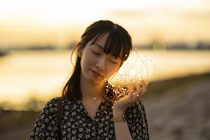 イルミネーションライトを耳に近づける若い女性の写真素材 [FYI04825570]
