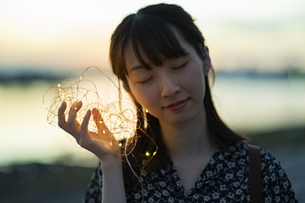 イルミネーションライトを耳に近づける若い女性の写真素材 [FYI04825571]
