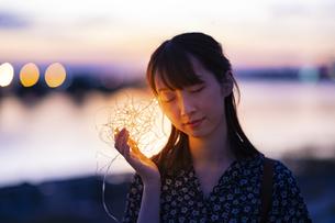 イルミネーションライトを耳に近づける若い女性の写真素材 [FYI04825572]