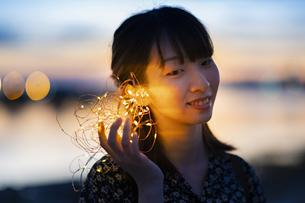 イルミネーションライトを耳に近づける若い女性の写真素材 [FYI04825573]