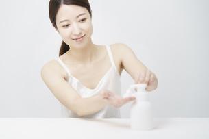 ボトルから泡を出す女性の写真素材 [FYI04825659]
