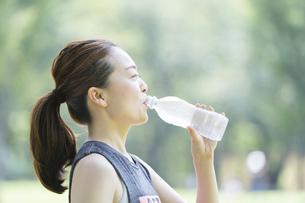 公園で運動(ヨガ)中に水分を補給する女性の写真素材 [FYI04825662]