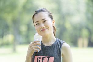 公園で運動(ヨガ)中に水分を補給する女性の写真素材 [FYI04825663]