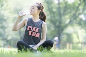 公園で運動(ヨガ)中に水分を補給する女性の写真素材 [FYI04825665]