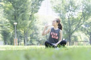 公園で運動(ヨガ)中に水分を補給する女性の写真素材 [FYI04825666]