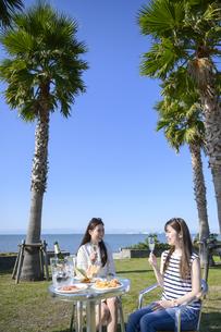 海のリゾートで食事する女性2人の写真素材 [FYI04826244]