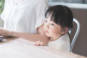 テレワークイメージ・リビングルームで仕事をする女性と遊ぶ子どもの写真素材 [FYI04826452]