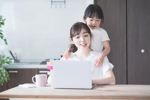 テレワークイメージ・リビングルームで仕事をする女性と遊ぶ子どもの写真素材 [FYI04826455]