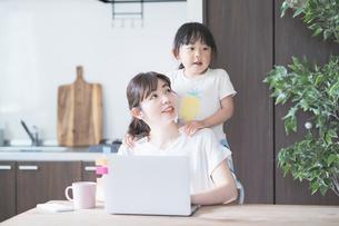 テレワークイメージ・リビングルームで仕事をする女性と遊ぶ子どもの写真素材 [FYI04826456]