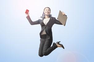 笑顔でジャンプする若いビジネスウーマン・就職活動生の写真素材 [FYI04826465]