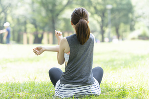 公園でヨガ・ストレッチをする女性の後ろ姿の写真素材 [FYI04827903]