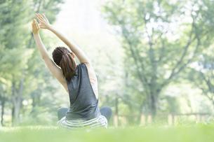 公園でヨガ・ストレッチをする女性の後ろ姿の写真素材 [FYI04827906]
