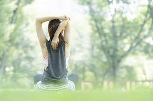 公園でヨガ・ストレッチをする女性の後ろ姿の写真素材 [FYI04827910]