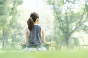公園でヨガ・ストレッチをする女性の後ろ姿の写真素材 [FYI04827911]
