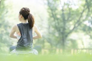 公園でヨガ・ストレッチをする女性の後ろ姿の写真素材 [FYI04827913]