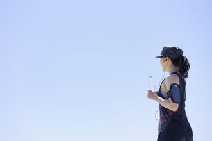ペットボトルを持つランニングウェア姿の女性と青空の写真素材 [FYI04828588]