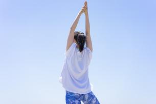 ヨガをする女性と青空の写真素材 [FYI04828595]