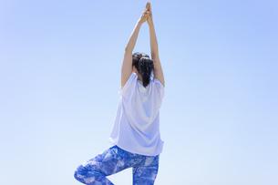 ヨガをする女性と青空の写真素材 [FYI04828596]