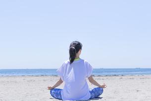 海辺でヨガをする女性の後ろ姿の写真素材 [FYI04828630]
