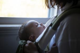 抱っこ紐に入って眠っている赤ちゃんの写真素材 [FYI04829280]