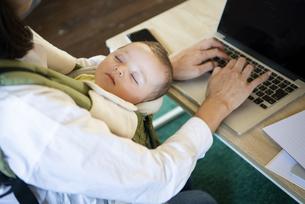 赤ちゃんを抱っこしながらパソコンで仕事をしている女性の写真素材 [FYI04829283]