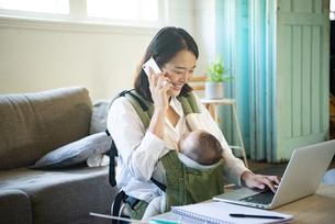 赤ちゃんを抱っこしながら家で仕事をしている女性の写真素材 [FYI04829285]