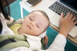 赤ちゃんを抱っこしながらパソコンで仕事をしている女性の手元の写真素材 [FYI04829286]