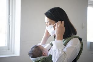 赤ちゃんを抱っこしながらマスクを付けている女性の写真素材 [FYI04829287]