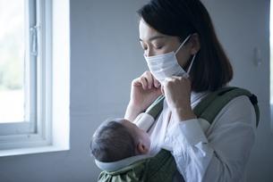 赤ちゃんを抱っこしながらマスクを付けている女性の写真素材 [FYI04829291]