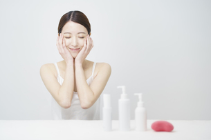 顔を触ってスキンケアをする女性と白いボトルの写真素材 [FYI04829650]