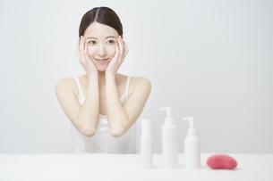 顔を触ってスキンケアをする女性と白いボトルの写真素材 [FYI04829651]