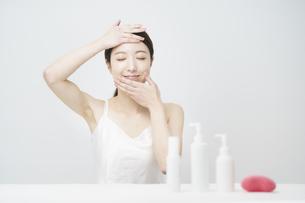 顔を触ってスキンケアをする女性と白いボトルの写真素材 [FYI04829652]