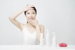 顔を触ってスキンケアをする女性と白いボトルの写真素材 [FYI04829653]