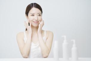 顔を触ってスキンケアをする女性と白いボトルの写真素材 [FYI04829654]