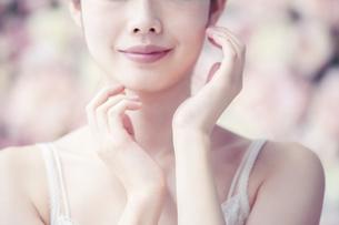 スキンケア・女性・フラワー背景・彩度弱めテイストの写真素材 [FYI04829669]