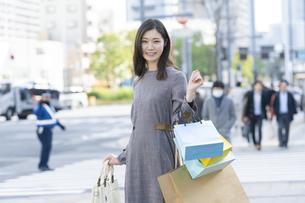たくさんの買い物袋を抱える女性の写真素材 [FYI04830405]
